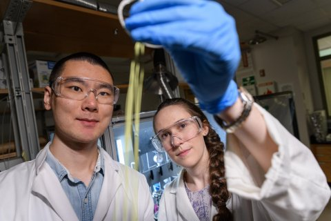 Fengyi Zhang and Emily K. McGuinness, graduate students at Georgia Tech, inspect a hollow fiber membrane that can be used for low-energy chemical separation. (Credit: Rob Felt)