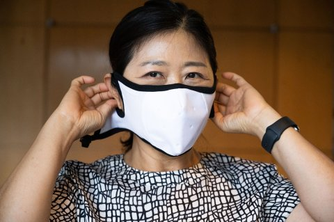 Sungmee Park puts on the mask, which was designed for better protection and comfort for the wearer. (Photo by Allison Carter)
